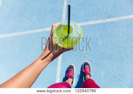 Runner drinking a healthy spinach green smoothie on outdoor running track getting ready for run. Clo