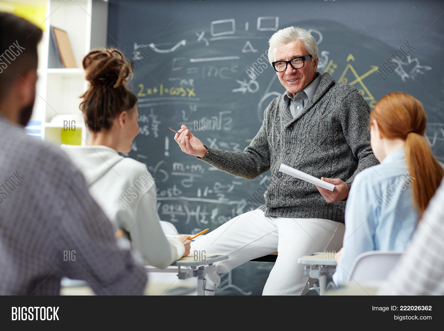 Friendly teacher talking to his students at lesson of algebra or trigonometry