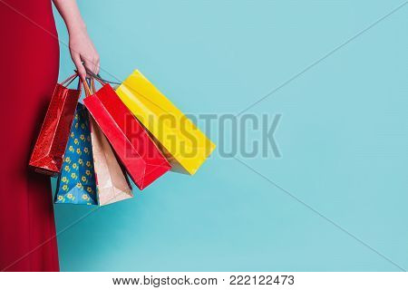 Girl in red dress with shopping bags on blue background. Black Friday shopping. A girl loves shopping. Shopping concept on a blue background. Stylish model with shopping bags. Do shopping on a black Friday