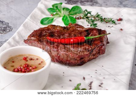 Top view close up, grilled beef steak with beer. rosemary, herbs and spices on gray concrete background. and glass of red wine on table, restaurant kitchen concept, view from above