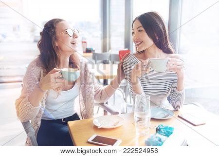 Pleasant moment. Happy brunette woman turning her head to her friend and keeping smile on face while joking all the time