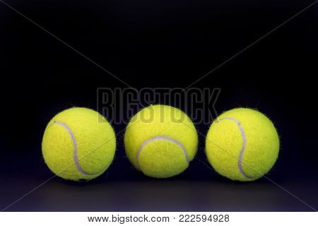 Yellow tennis balls on black background. Tennis ball abstract photo for banner template. Sport equipment isolated. Tennis competition backdrop. Yellow felt ball for active game. Outdoor sport activity stock photo