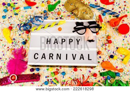Lightbox with letters - HAPPY CARNEVAL - on colorful festive party decoration with steamers, confetti and ballons. stock photo