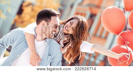 Happy Young Couple Sitting On A Bench Together.