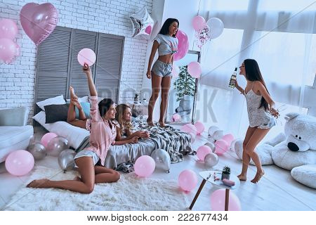 Four attractive young women in pajamas bonding together while having a slumber party in the bedroom with balloons all over the place