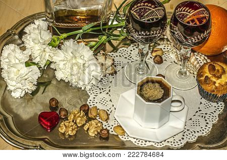 Black coffee and carnations,old crystal glasses with a bottle of liqueur, nuts and an orange, pearl beads, shells on a tray of nickel silver stock photo