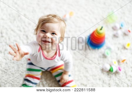Adorable cute beautiful little baby girl playing with educational toys at home or nursery. Happy healthy child having fun with colorful wooden rainboy toy pyramid. Kid learning different skills