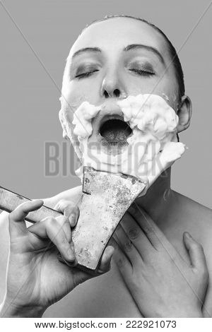 beautiful woman with fake mustache, beard on pink background has shave with axe, monochrome stock photo