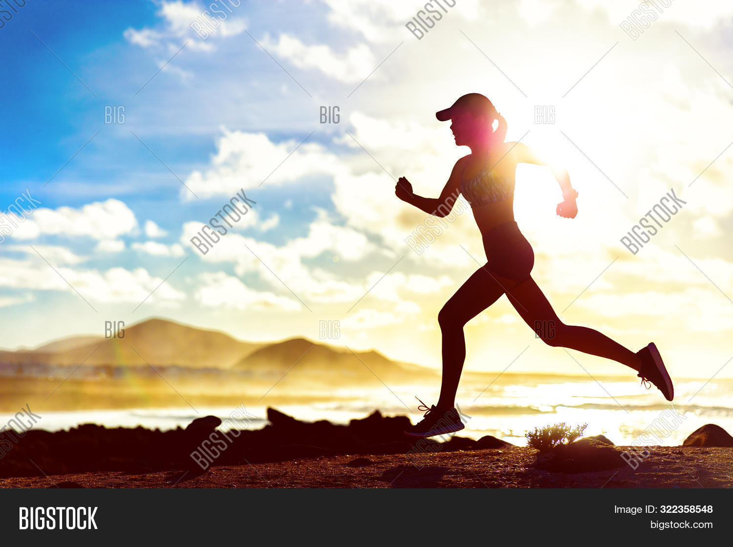 Running fitness girl jogging through landscape beach background at sunset sprinting with speed and m