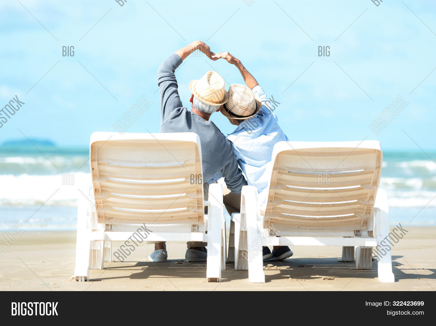 Asian Lifestyle senior couple raise hands and sitting on the beach happy in love romantic and relax time. Tourism elderly family travel leisure and activity after retirement vacations and summer.