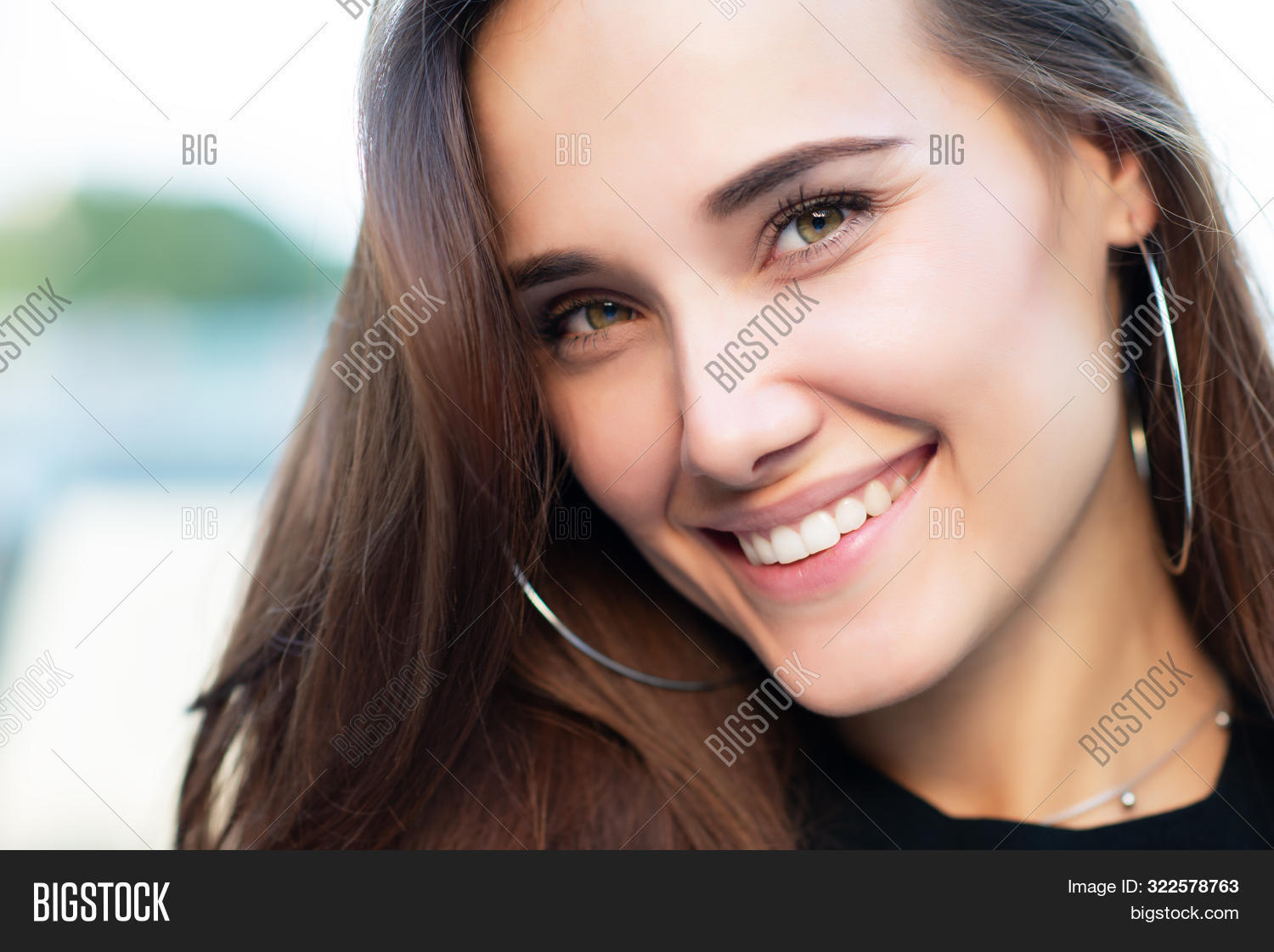 Young attractive woman with perfect smile, summer outdoor portrait. Charming cheerful girl smiling a