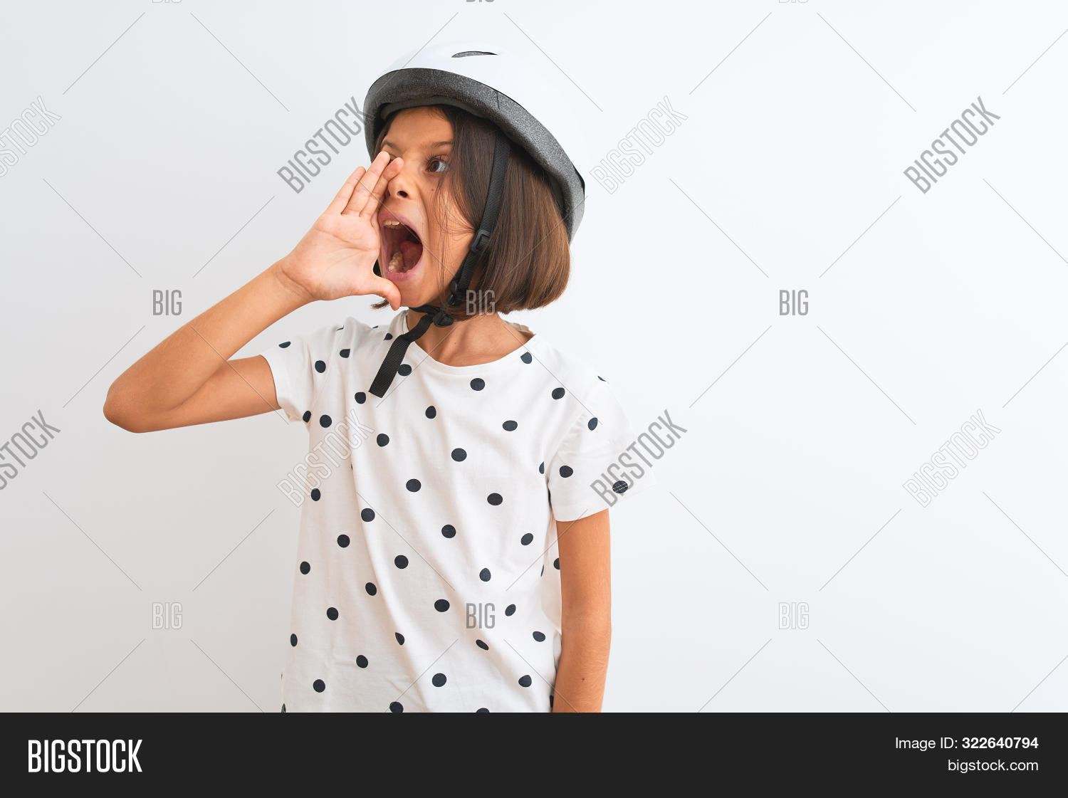 Beautiful child girl wearing security bike helmet standing over isolated white background shouting a