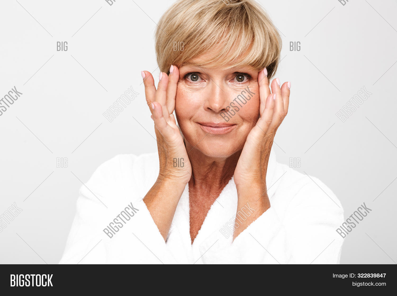 Image of attractive adult woman with short blond hair wearing white housecoat touching her face isol