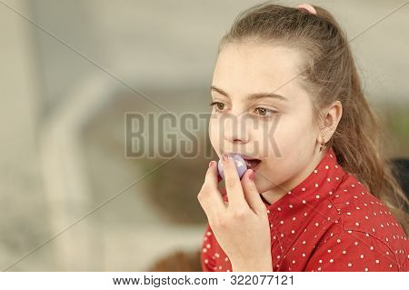 Pure beauty. Beauty girl putting on lip balm makeup. Beauty look of adorable small girl. Little child with cute beauty face and blonde hair, copy space. stock photo