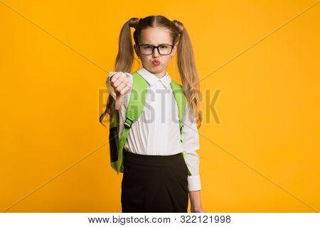 Dislike. Discontented Schoolgirl Gesturing Thumbs Down Standing Over Yellow Studio Background. Copy Space stock photo