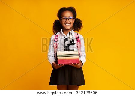 Adorable Afro Schoolgirl Holding Microscope And Stack Of Books On Yellow Studio Background. Free Space stock photo