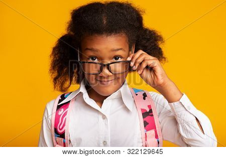 Portrait Of Afro Elementary Student Girl Looking Over Eyeglasses At Camera. Studio Shot, Yellow Background stock photo