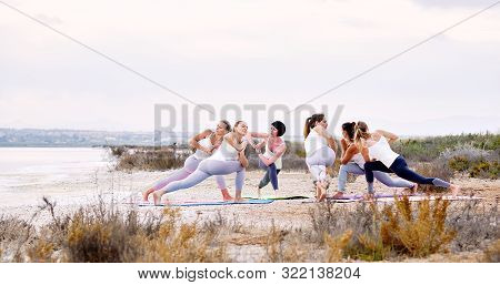 Six attractive women in sportswear doing yoga outdoors, standing on mat in circle on nature performing Side Angle Pose or Parivrtta Parsvakonasana, asana exercise strengthens body improves balance stock photo