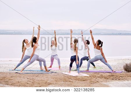 Full-length group of yogi women wearing activewear practising yoga outdoors standing on mats performing Warrior pose doing Virabhadrasana exercise on nature near lake, healthy lifestyle hobby concept stock photo