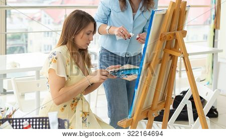 Art class, drawing and creativity concept - Close-up of female student sitting in front of easel with palette and paintbrush. Teacher helps her stock photo