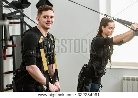 Man and woman in EMS suits doing suspension training stock photo