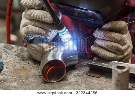 Young Guy Welder In A Checkered Red Shirt Welds A Stainless Steel Pipe Using Agronomic Welding To Pr