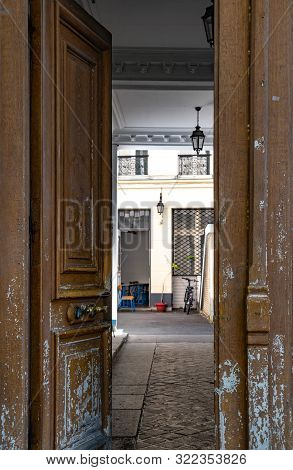 Opened double door with flaking brown and grey painted layers. Old wooden door to patio inside stone building in Paris France. Vintage scratched framed door details. City life scene. Travel Europe. stock photo
