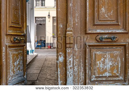 Shabby double door surface with flaking brown and grey paints. Opened door to courtyard inside old house in Paris France. Vintage framed door details. City life scene. Travel Europe. stock photo
