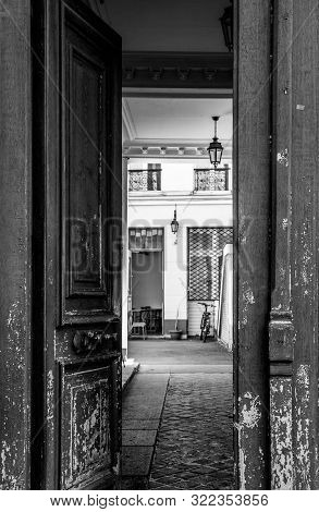 Black and white photography of shabby double door surface with flaking paint. Opened door to courtyard inside old house in Paris France. Vintage framed door details. City life scene. Travel Europe. stock photo