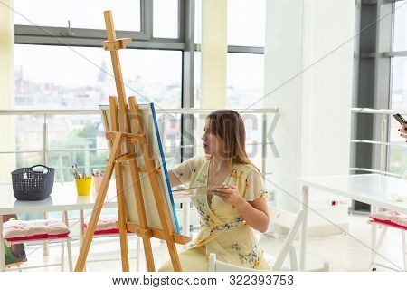 Art class, drawing and creativity concept - Female student sitting in front of easel with palette and paintbrush stock photo