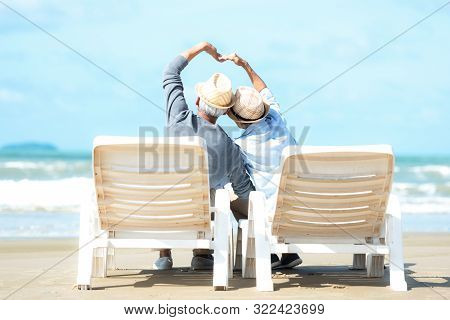 Asian Lifestyle senior couple raise hands and sitting on the beach happy in love romantic and relax time. Tourism elderly family travel leisure and activity after retirement vacations and summer. stock photo
