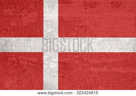 Denmark flag on an old painted tattered wooden surface. Textured background for design. stock photo