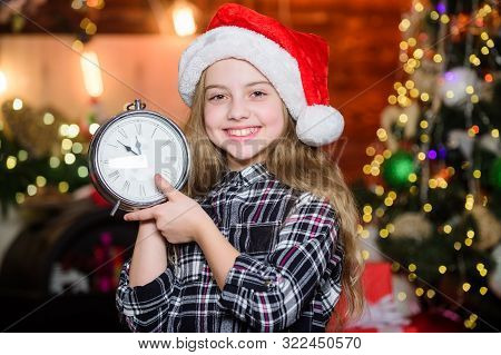 Magic moment is coming. Christmas almost here. Girl santa claus hat and clock. Meet Christmas holiday. Festive atmosphere christmas day. New year countdown. Counting time. Few minutes till new year stock photo