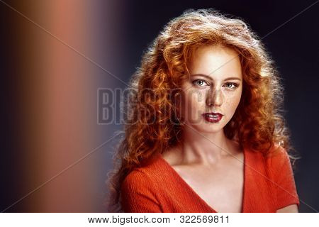 Beauty portrait. Charming girl with long red curly hair over black background. Hair care, hair coloring. Copy space. stock photo