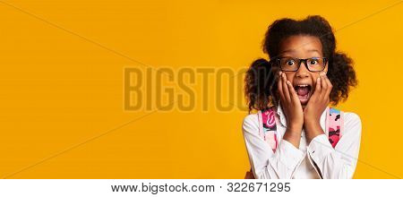 Scared African American Schoolgirl Shouting With Fear Over Yellow Background In Studio. Panorama, Copy Space stock photo