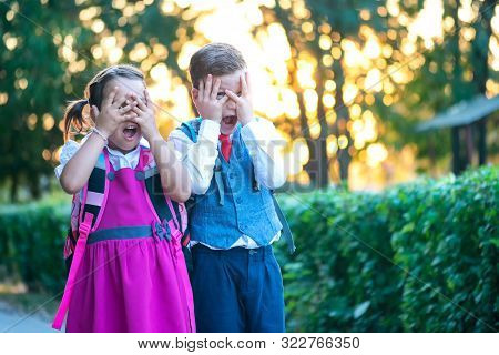A boy and a girl with backpacks and being afraid of the first day of school stock photo