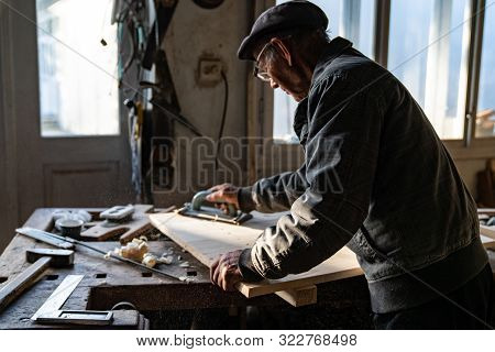 Old senior carpenter in grey clothes and glasses working at home, polishes wood stock photo