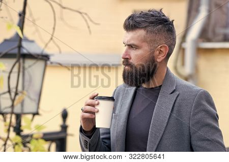 Hipster hold paper coffee cup and enjoy park environment. Relaxing coffee break. Drink it on the go. Man bearded hipster prefer coffee take away. Businessman bearded guy drink coffee outdoors. stock photo