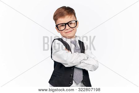 Smirking kid in glasses and formal outfit with crossed arms standing over white background stock photo