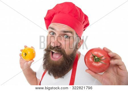 Cook in uniform holds vegetables. Ripe tomato for delicious meal. Eat fresh tomato. Pick one. Tomato sauce recipe. Healthy cooking concept. Man with beard on white background. Chef holds tomatoes. stock photo