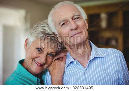 Portrait of senior couple smiling in living room at home stock photo
