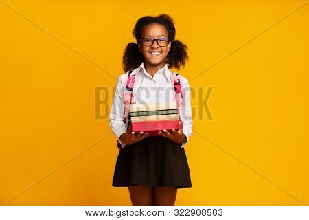 Back To School. Excited African American First-Grade Schoolgirl Holding Stack Of Books On Yellow Background In Studio. Free Space stock photo
