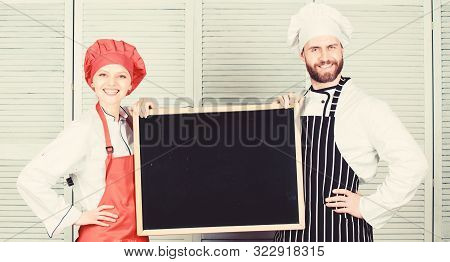 Learning to cook through cook. Master cook and kitchen maid giving cooking class. Couple of man and woman holding empty board in cooking school. Chef and helper teaching master class, copy space stock photo