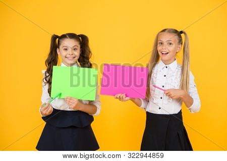 Important lesson you should learn. Cute small children reciting lesson with pen and paper on yellow background. Little girls having lesson in writing. Using exciting ideas in the lesson, copy space. stock photo