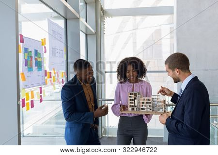 Front view of a young African American female architect with a young African American and a young Caucasian male architect holding an architectural model. The three of them are standing in discussion stock photo