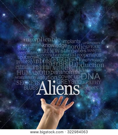 Are you Alien Aware Word Cloud - female hand with the word ALIENS floating above surrounded by a relevant word cloud against a cosmic dark blue night sky background stock photo