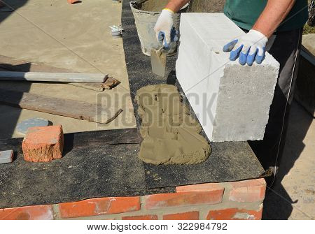 Bricklayer builder laying autoclaved aerated concrete blocks for house foundation wall with waterproofing bitumen membrane stock photo