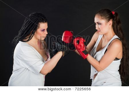 two white girls are boxing with mufflers on black background stock photo