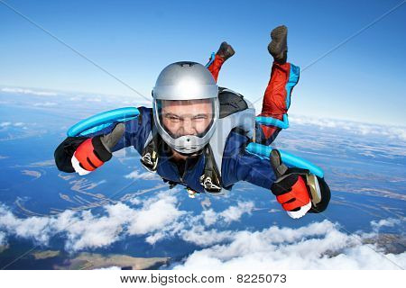 Skydiver falls through the air. All right! Thumbs up! Parachuting is fun! stock photo