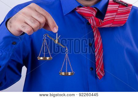 Businessman with red tie and blue shirt holding golden scales unbalanced isolated on white background. stock photo